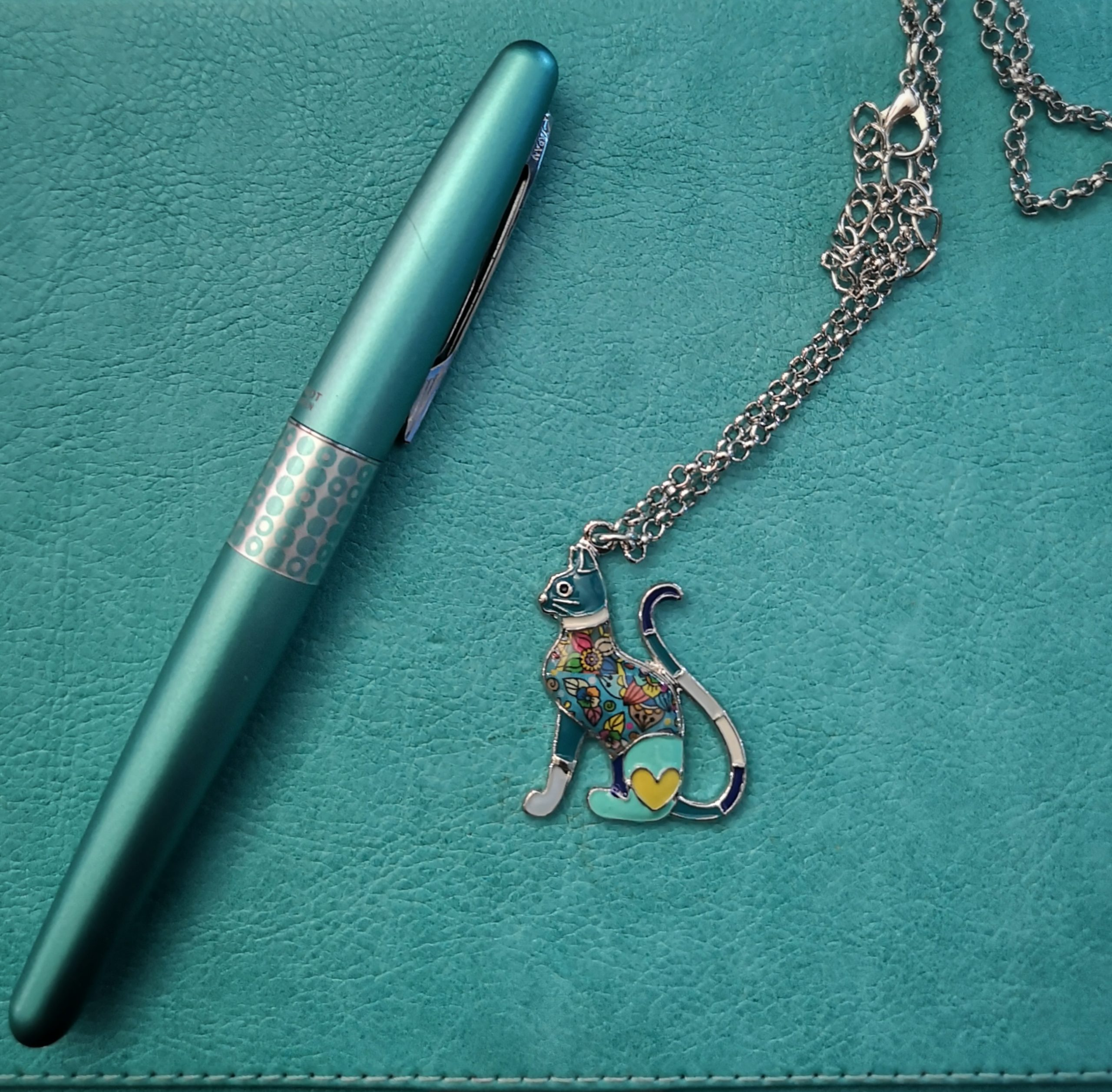 Teal color binded book with teal color ink pen and teal accent cat pendant necklace.